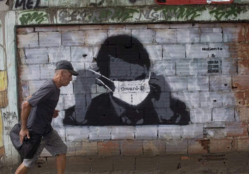 A man walks past a graffiti of Brazil's President Jair Bolsonaro wearing a protective mask during the new coronavirus outbreak in Rio de Janeiro, Brazil. (AP Photo/Silvia Izquierdo)