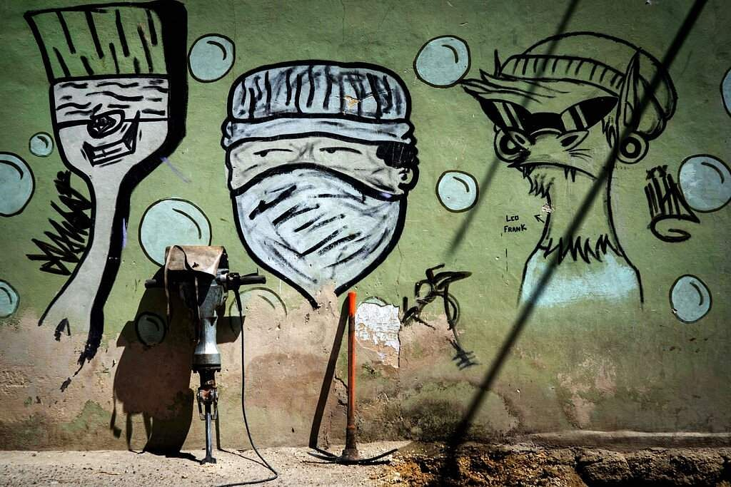 Street art of a man wearing a mask covers a wall where tools from workers repairing a water pipe stand in Havana, Cuba. (AP Photo/Ramon Espinosa)