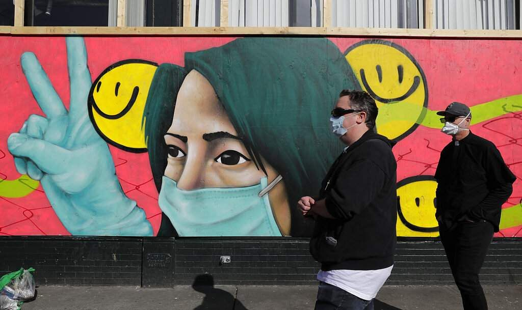Pedestrians walk past coronavirus-themed artwork painted by street artists @theydrift and @ksra_ksra on a boarded-up business in Seattle's Capitol Hill neighbourhood. (AP Photo/Ted S Warren)