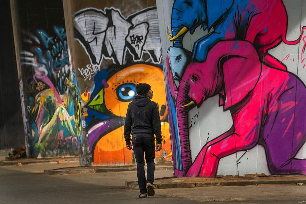 A man walks by graffiti in the near-deserted Hip Maboneng district of downtown Johannesburg, South Africa. (AP Photo/Jerome Delay)