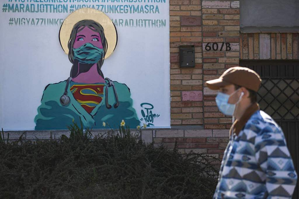 A man wearing a face mask walks past a graffiti with the inscription reading, 'Stay at home and let's take care of each other' in Erd, south of Budapest, Hungary. (Marton Monus/MTI via AP)