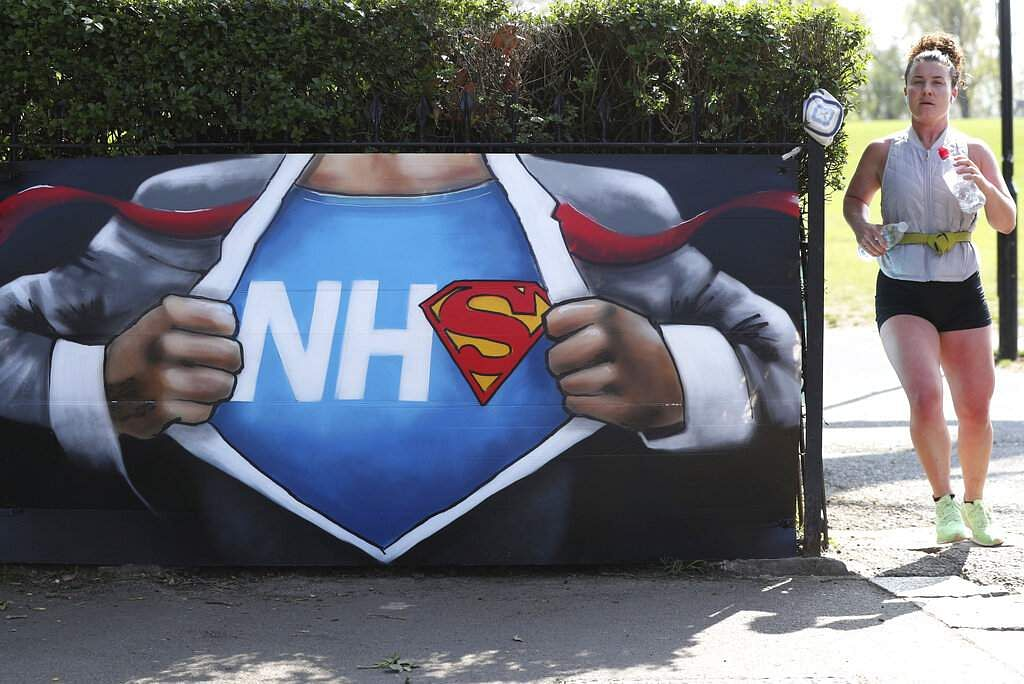 A runner passes street art in appreciation of the NHS placed near the Francis Drake Bowls Club in Hilly Fields Park, in Lewisham, London. (Jonathan Brady/PA via AP)