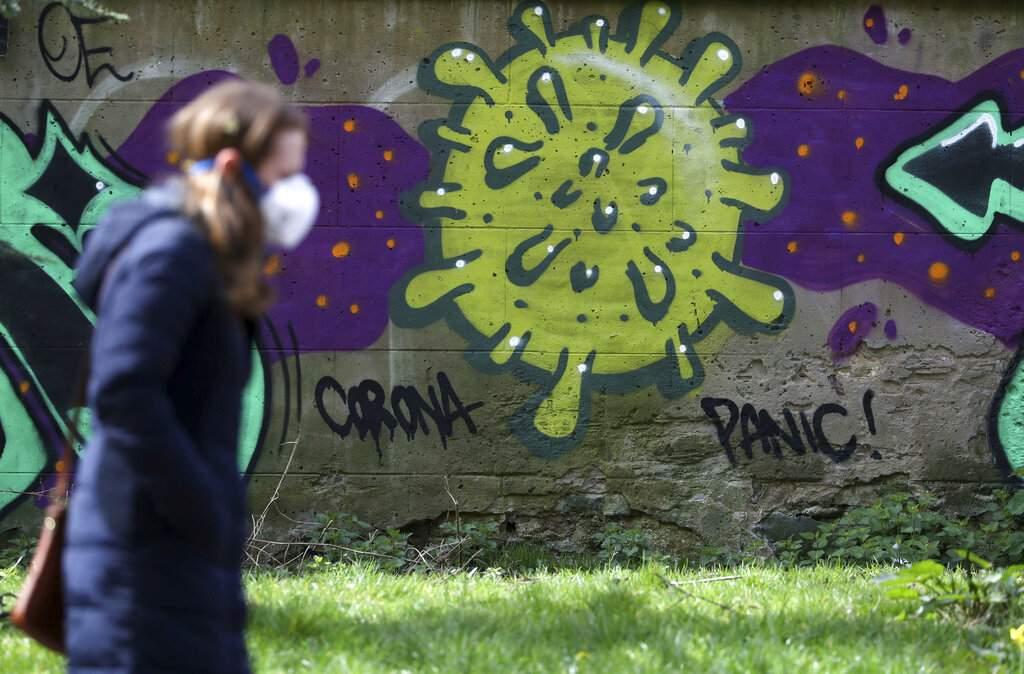 A woman walks past coronavirus-related graffiti in Edinburgh, Scotland as the UK continues in lockdown to help curb the spread of the coronavirus. (Andrew Milligan/PA via AP)