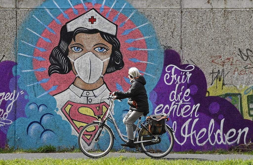 A woman cycles past a coronavirus graffiti by street artist 'Uzey' showing a nurse as Superwoman. The lettering reads 'For the real heroes', on a wall in Hamm, Germany. (AP Photo/Martin Meissner)