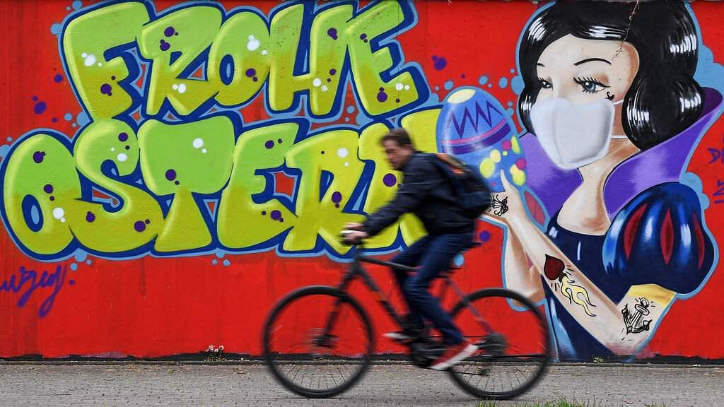 A cyclist passes a coronavirus graffiti reading 'Happy Easter' on a wall in Hamm, Germany, on Easter Monday. (AP Photo/Martin Meissner)