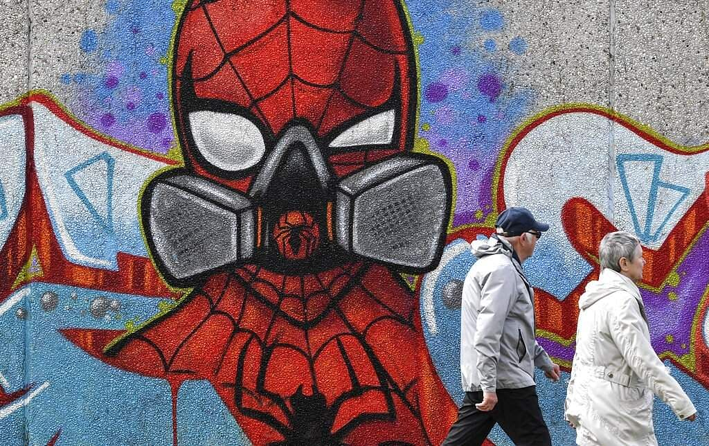 People walk past a coronavirus graffiti by street artist 'Uzey' showing Spiderman with a protection mask on a wall in Hamm, Germany. (AP Photo/Martin Meissner)