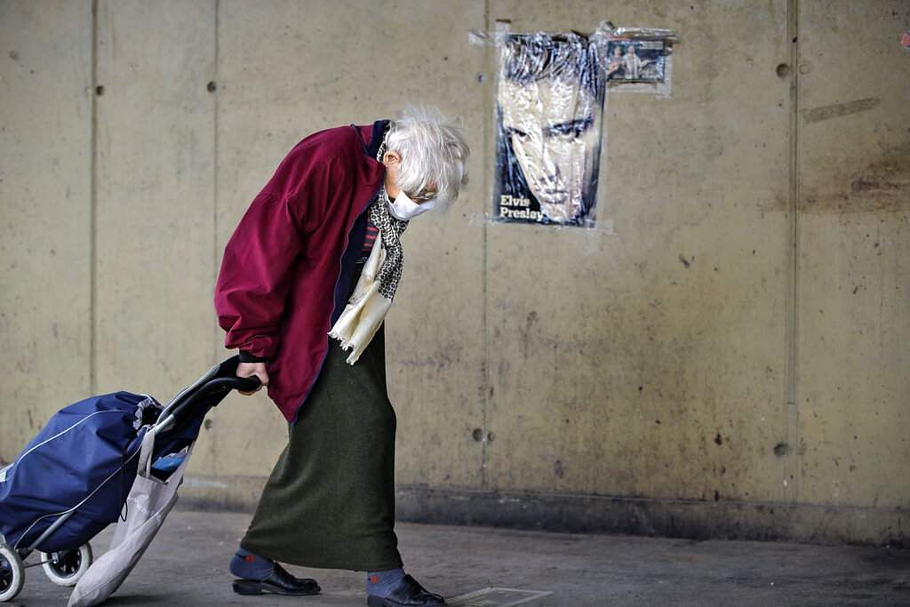 An elderly woman drags a shopping trolley, backdropped by an Elvis Presley poster, at a market place in Bucharest, Romania. (AP Photo/Vadim Ghirda)