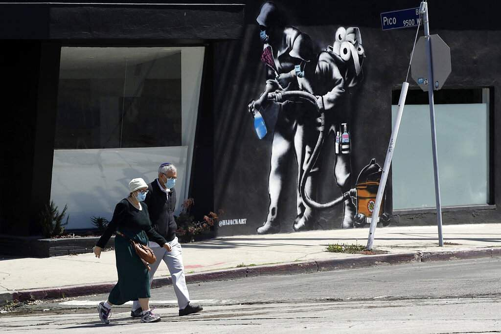 People wearing masks walk past a mural depicting a coronavirus theme during the COVID-19 pandemic, in Los Angeles. (AP Photo/Marcio Jose Sanchez)