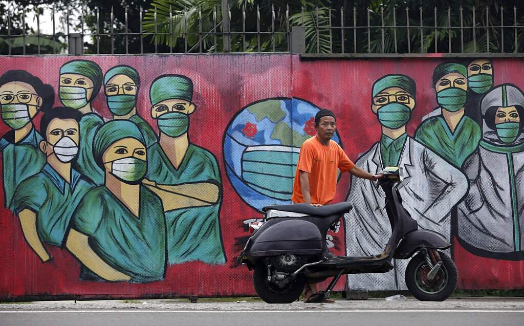 A motorist in front a mural painted as a tribute to medical workers in Depok, on the outskirts of Jakarta, Indonesia. (AP Photo/Dita Alangkara)