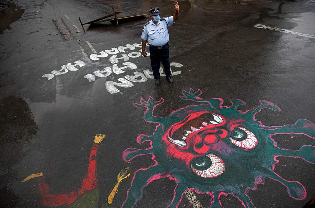 An Indian traffic policeman stands next to an artwork displayed on a road to create awareness about coronavirus during lockdown in Gauhati, Assam. (AP Photo/Anupam Nath)