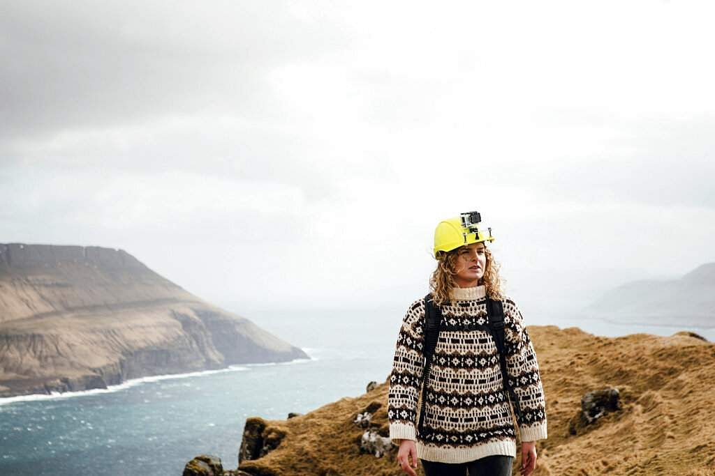 A tour guide for Visit Faroe Islands wears a helmet with a live-streaming camera (Kirstin Vang/Visit Faroe Islands via AP)