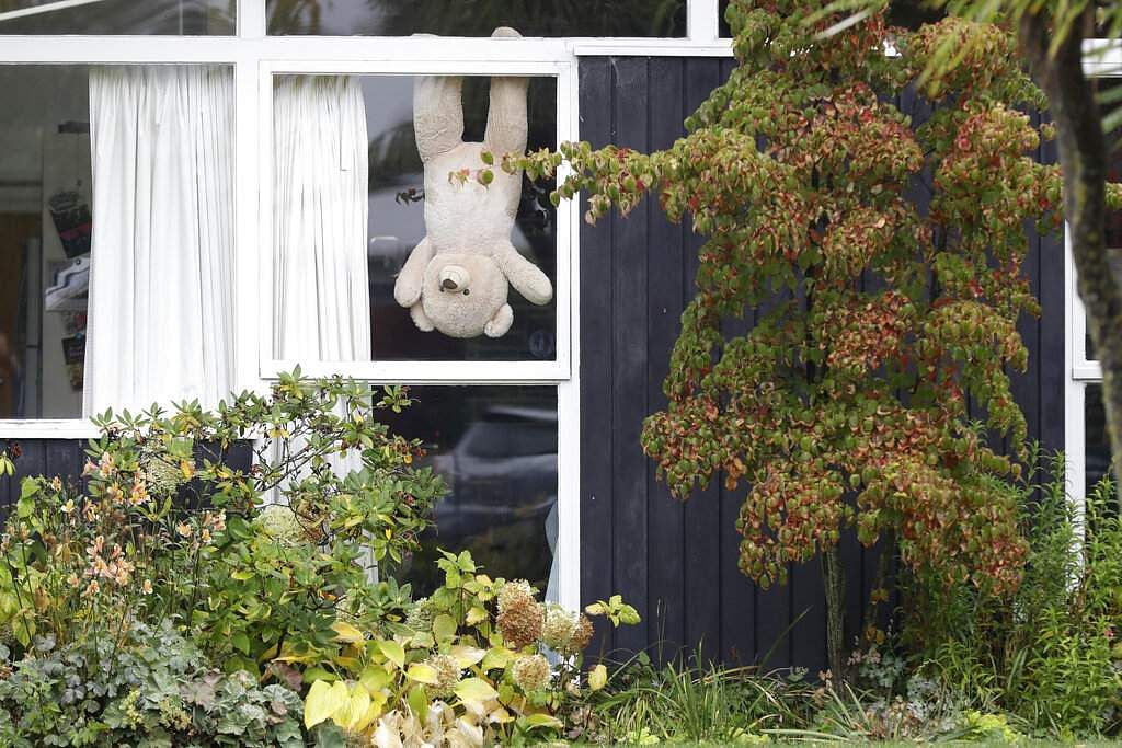 A teddy bear hangs in a window of a house in Christchurch. New Zealanders are embracing a global movement in which people place teddies in their windows to brighten the mood. (AP Photo/Mark Baker)