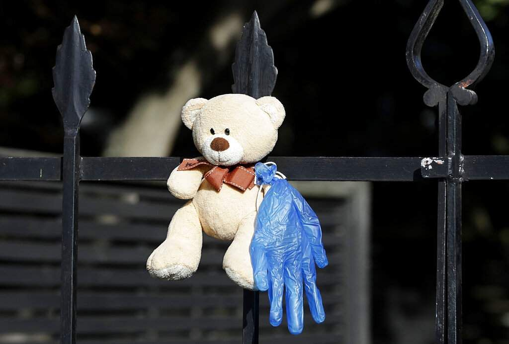 A teddy bear hangs on a fence at a house in Christchurch. New Zealanders are embracing a global movement in which people place teddies in their windows to brighten the mood. (AP Photo/Mark Baker)