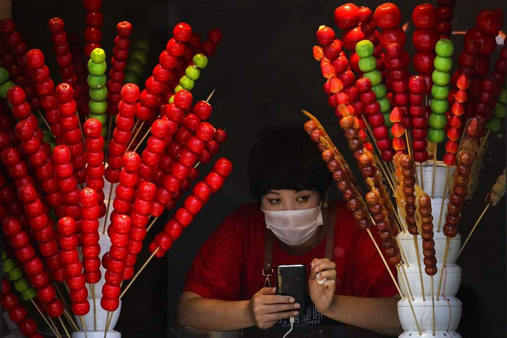 A vendor wearing a face mask looks out of her store selling sugar-coated haws on a stick in Beijing, China. (AP Photo/Andy Wong)