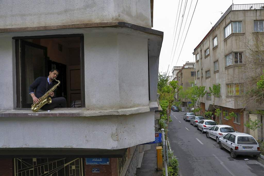 Mohammad Maleklee, 23, of the National Orchestra of Iran and Tehran Symphony, plays saxophone in his window, during mandatory self-isolation in Tehran, Iran. (AP Photo/Ebrahim Noroozi)
