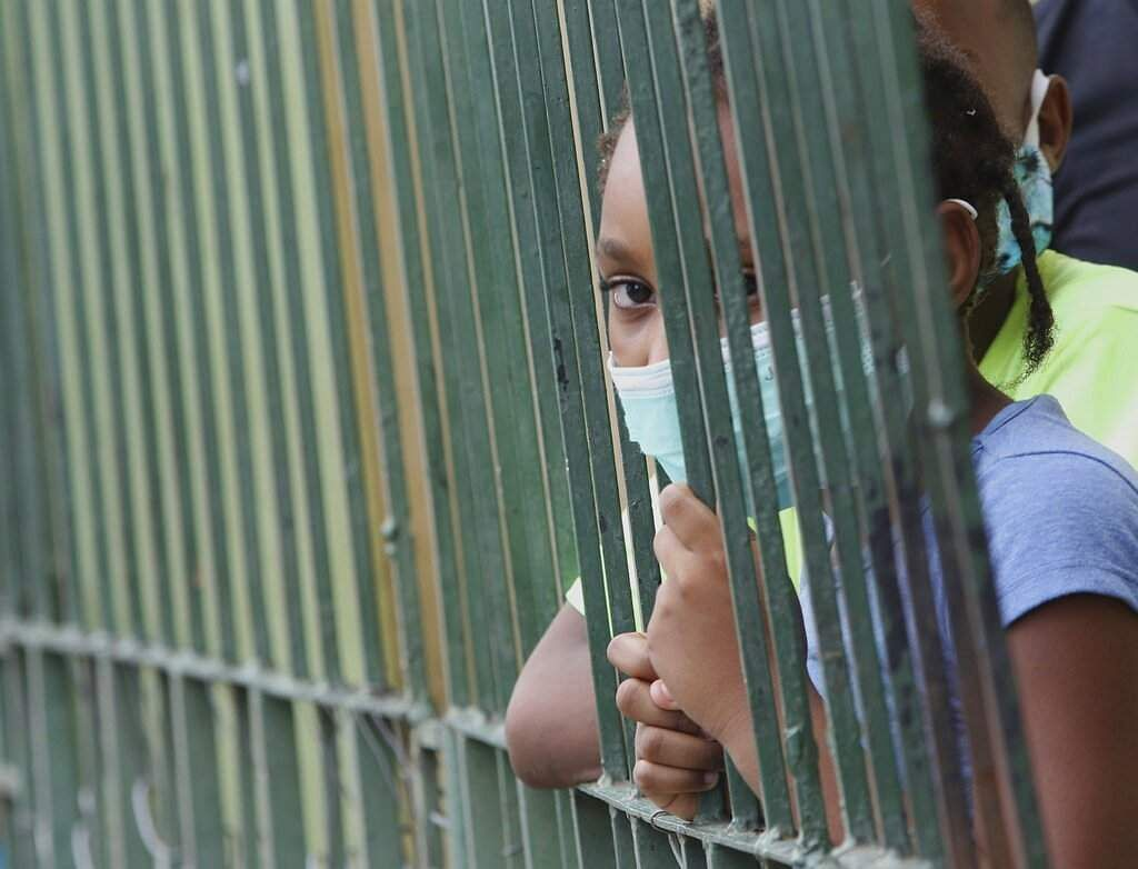 A girl wearing a mask looks from her home in the neighborhood of Cristo del Consuelo as her family waits for food handouts in Guayaquil, Ecuador. (AP Photo/Angel de Jesus)