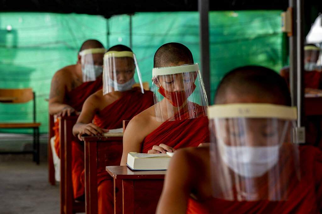 Novice Buddhist monks with protective masks and face shields, seated maintaining social distancing participate in a religious class in Bangkok, Thailand. (AP Photo/Gemunu Amarasinghe)