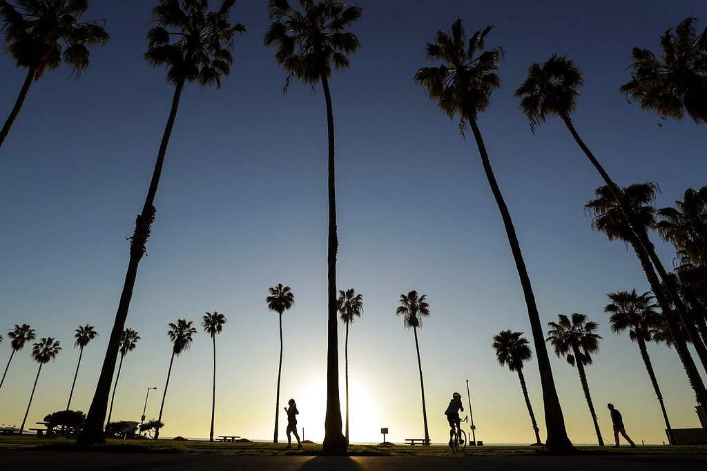People keep their distance as they exercise outside of a closed La Jolla beach, in San Diego. (AP Photo/Gregory Bull)