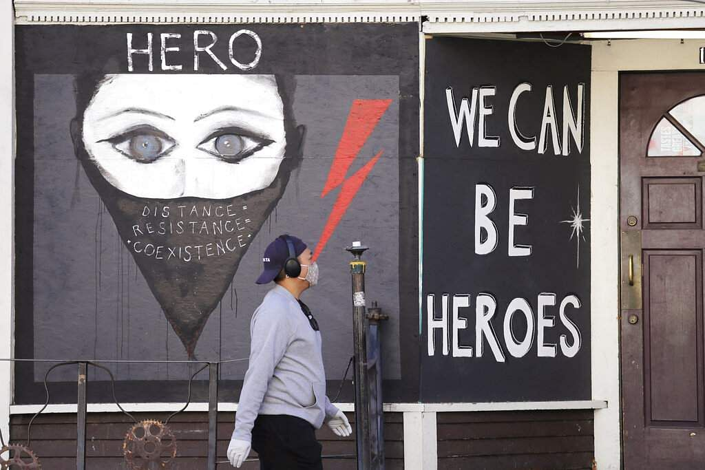 A pedestrian walks past artwork painted on plywood covering a business closed during the coronavirus outbreak in Seattle. (AP Photo/Elaine Thompson)