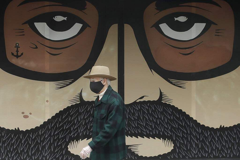 A man wearing a protective face mask walks in front of a closed building in San Francisco. (AP Photo/Jeff Chiu, File)