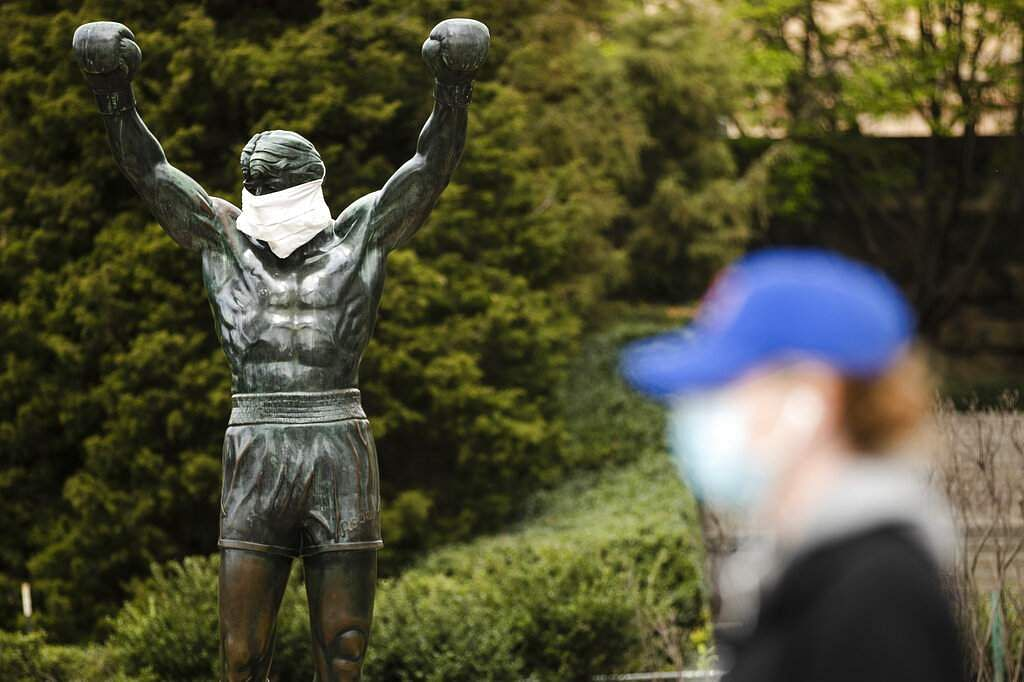 A person wearing a protective face mask walks past a Rocky statue outfitted with a mock surgical face mask at the Philadelphia Art Museum in Philadelphia. (AP Photo/Matt Rourke, File)