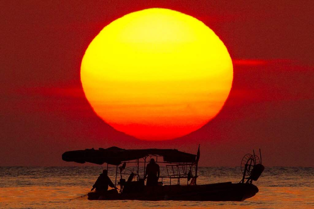 The sun sets as a fishing boat crosses the Mediterranean Sea at Ramlet al-Baida public beach, during a lockdown to curbing the spread of COVID-19, in Beirut, Lebanon. (AP Photo/Hassan Ammar)