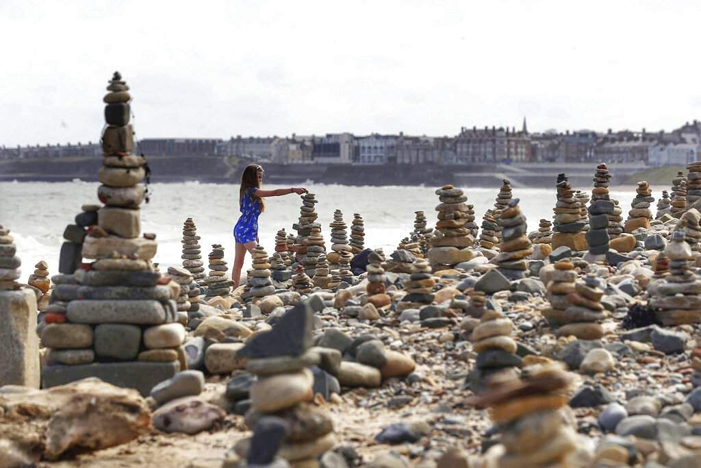 A girls adds a pebble to a sculpture on Whitley Bay beach on the North East coast of England, during the lockdown to stop the coronavirus. (Owen Humphreys/PA via AP)