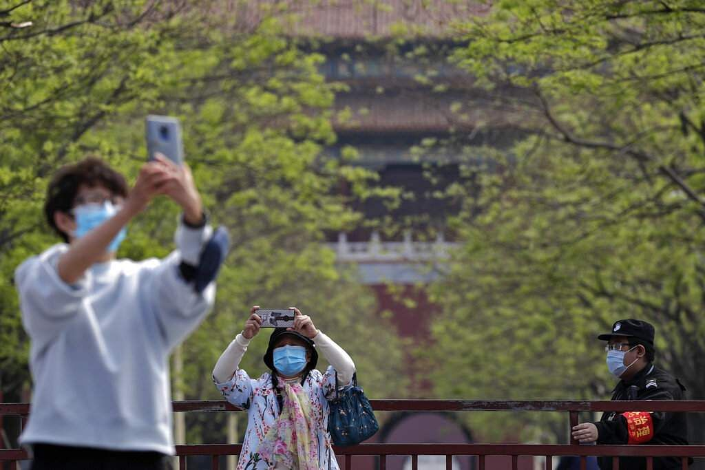 Women wearing protective face masks take souvenir photos outside the closed gate of the Forbidden City, usually crowded with tourists, in Beijing, China. (AP Photo/Andy Wong)
