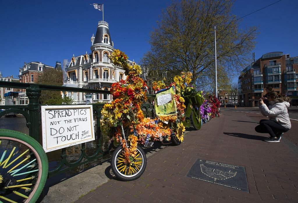 A woman takes images of decorated bicycles, or flower bikes, as a sign warns about the risk of spreading the coronavirus in Amsterdam, Netherlands. (AP Photo/Peter Dejong)