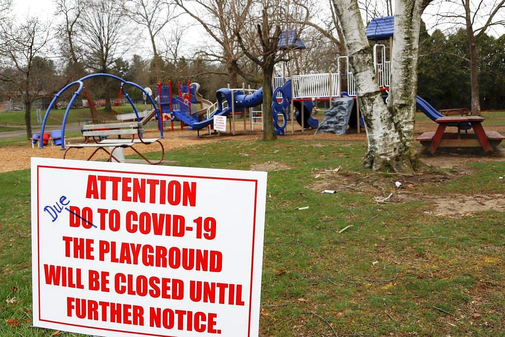 A sign with corrected spelling tells visitors the playground at the Community Park is closed until further notice due to COVID-19 in Zelienople, Pa. (AP Photo/Keith Srakocic)