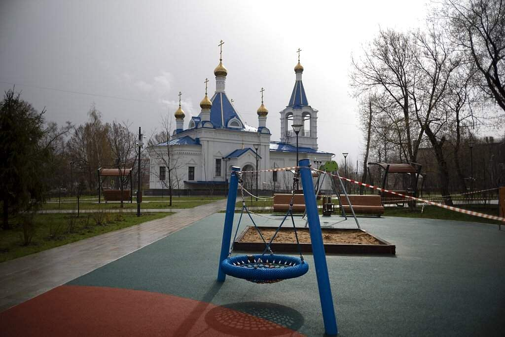 A caution tape cordons off an empty children's playground with a church seen in the background, officially closed to the order of the city in Moscow, Russia. (AP Photo/Alexander Zemlianichenko)