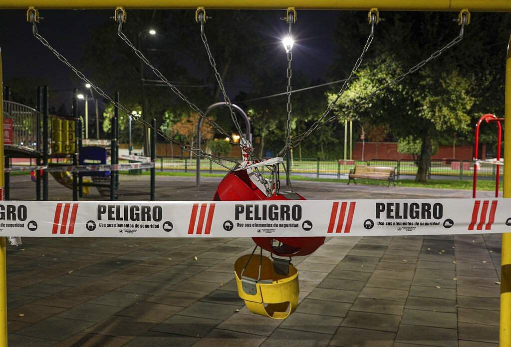 A swing set at a public playground area is closed with security tape that reads in Spanish 'Danger,' as a precautionary measure in Santiago, Chile. (AP Photo/Esteban Felix)