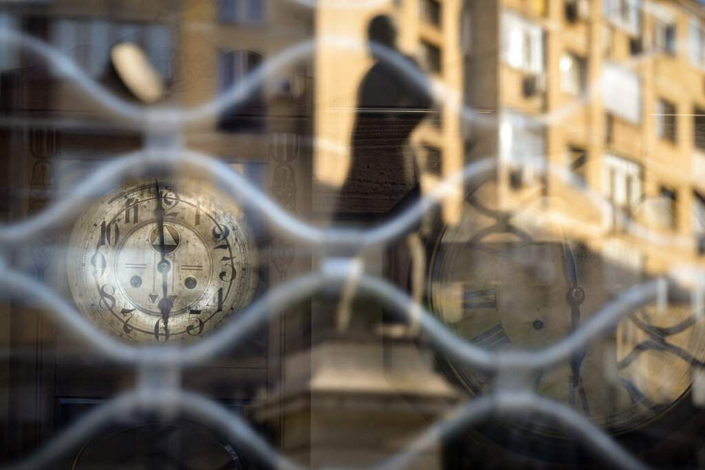 Apartment blocks are reflected in the window of a vintage clock repair shop in Bucharest, Romania at 1800 on Friday, April 24, 2020. (AP Photo/Andreea Alexandru)