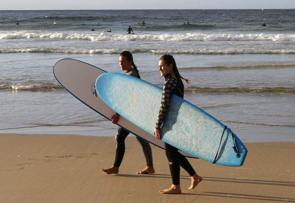 Surfers walk onto the sand to enter the water at Bondi Beach in Sydney as the pandemic restrictions are eased. The beach is open to swimmers and surfers to exercise only. (AP Photo/Rick Rycroft)