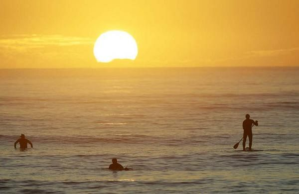 Surfers prepare to enter the water at Sumner Beach as level four COVID-19 restrictions are eased in Christchurch, New Zealand. (AP Photo/Mark Baker)
