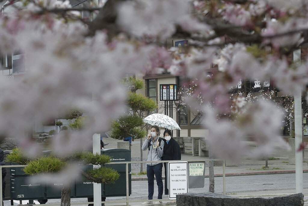 A man and woman are shown through cherry blossom trees wearing masks while waiting in line to enter a market in Japantown in San Francisco, US. (AP Photo/Jeff Chiu)
