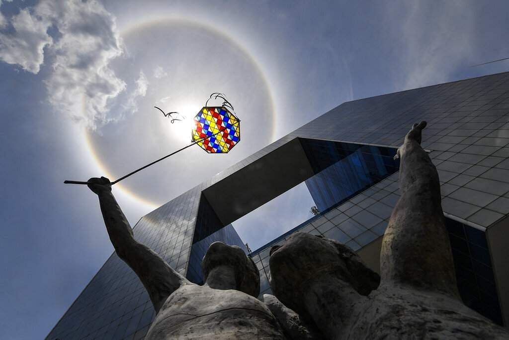 A sculpture by artist Teresa Cabello is seen with a solar halo in the background during a govt-imposed quarantine to stop the COVID-19 outbreak in Caracas, Venezuela. (AP Photo/Matias Delacroix)