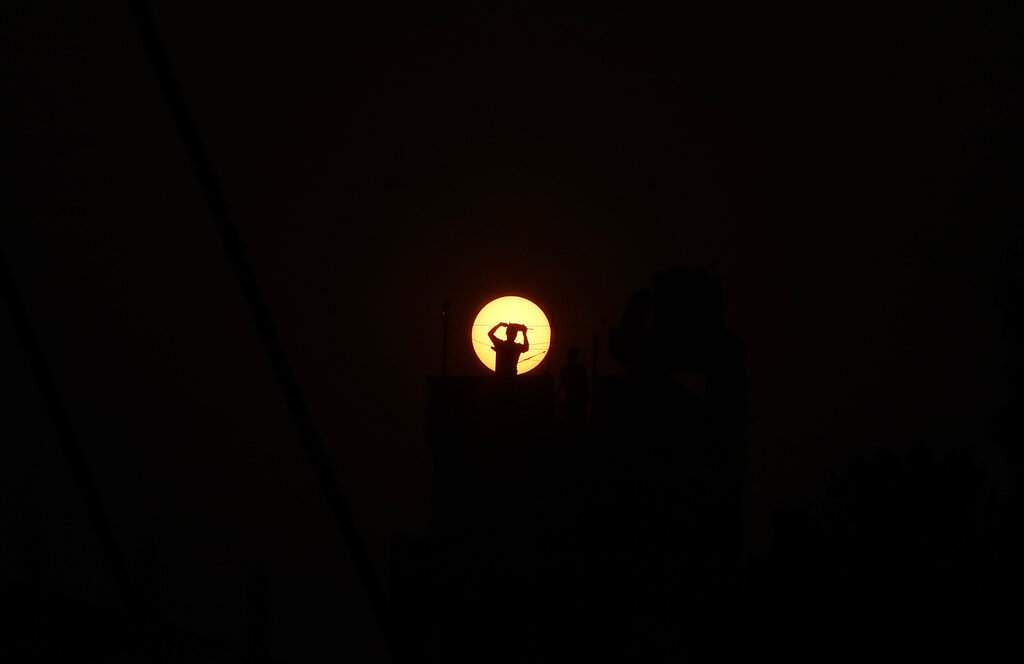 A Nepalese man flying a kite on the roof top of his house is silhouetted against the setting sun during lockdown in Kathmandu, Nepal. (AP Photo/Niranjan Shrestha)