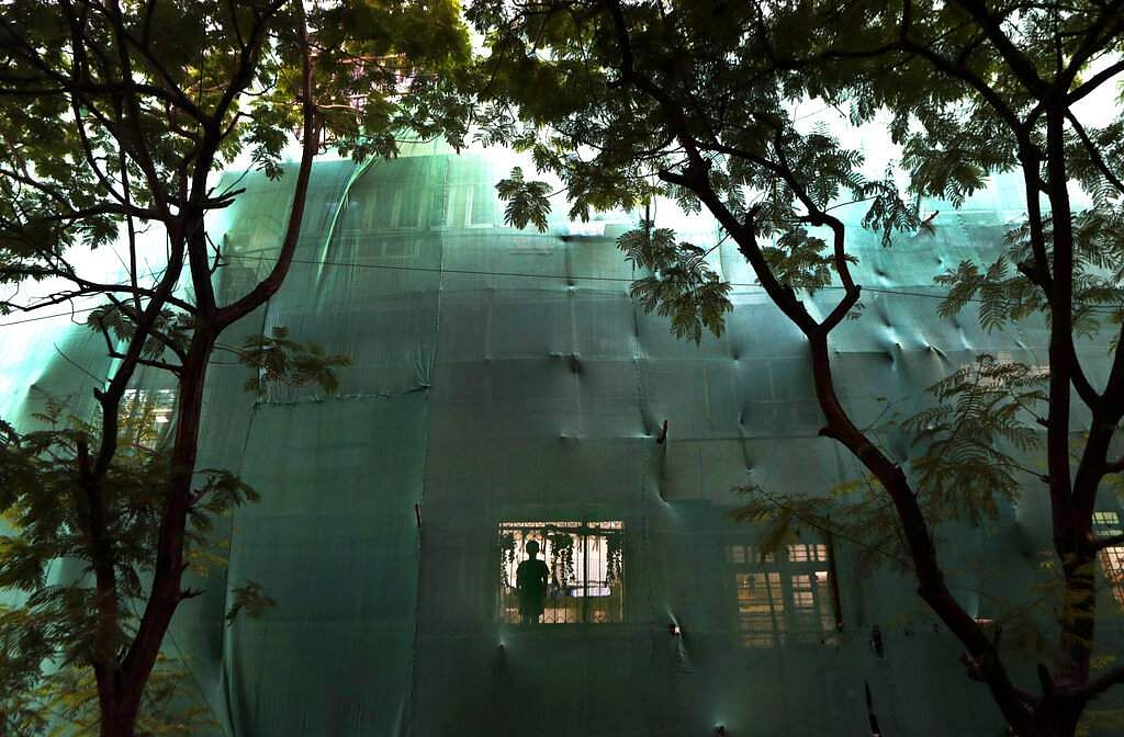 A boy looks out from the window of his house of a residential building covered with a green cloth for repairs during the coronavirus pandemic lockdown in Mumbai. (AP Photo/Rajanish Kakade)