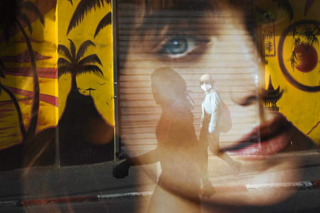 A woman is reflected on a bus station as she wears a protective face mask amid concerns over the country's coronavirus outbreak, in Tel Aviv, Israel. (AP Photo/Oded Balilty)