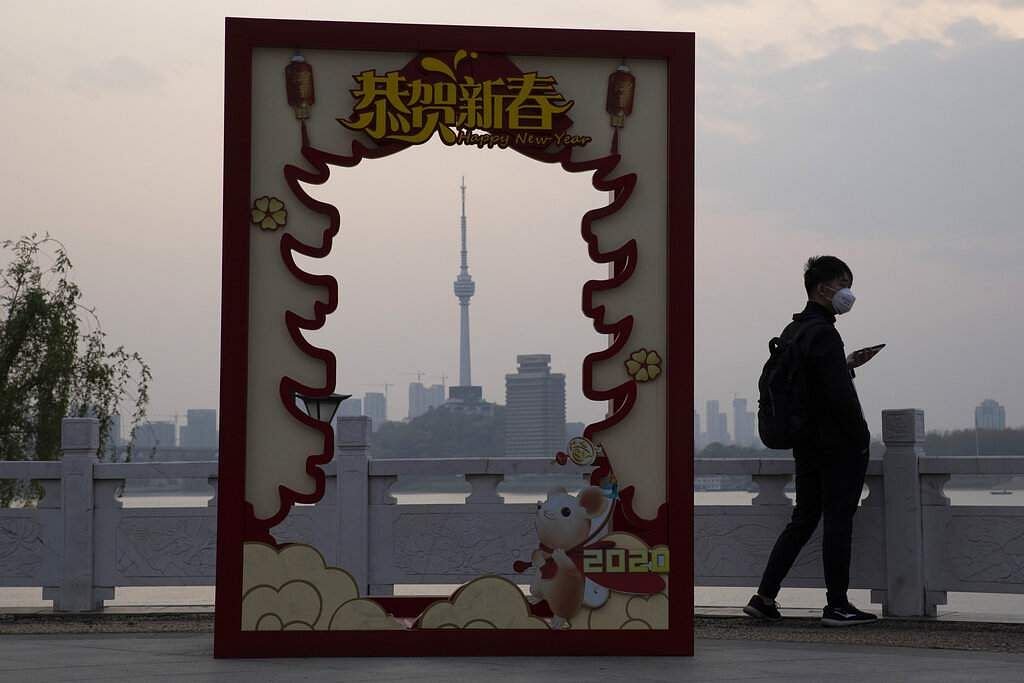 A man wearing a mask passes by a board in the shape of a pagoda framing the Tortoise Mountain TV Tower in Wuhan, where the virus quarantine has finally been lifted. (AP Photo/Ng Han Guan)