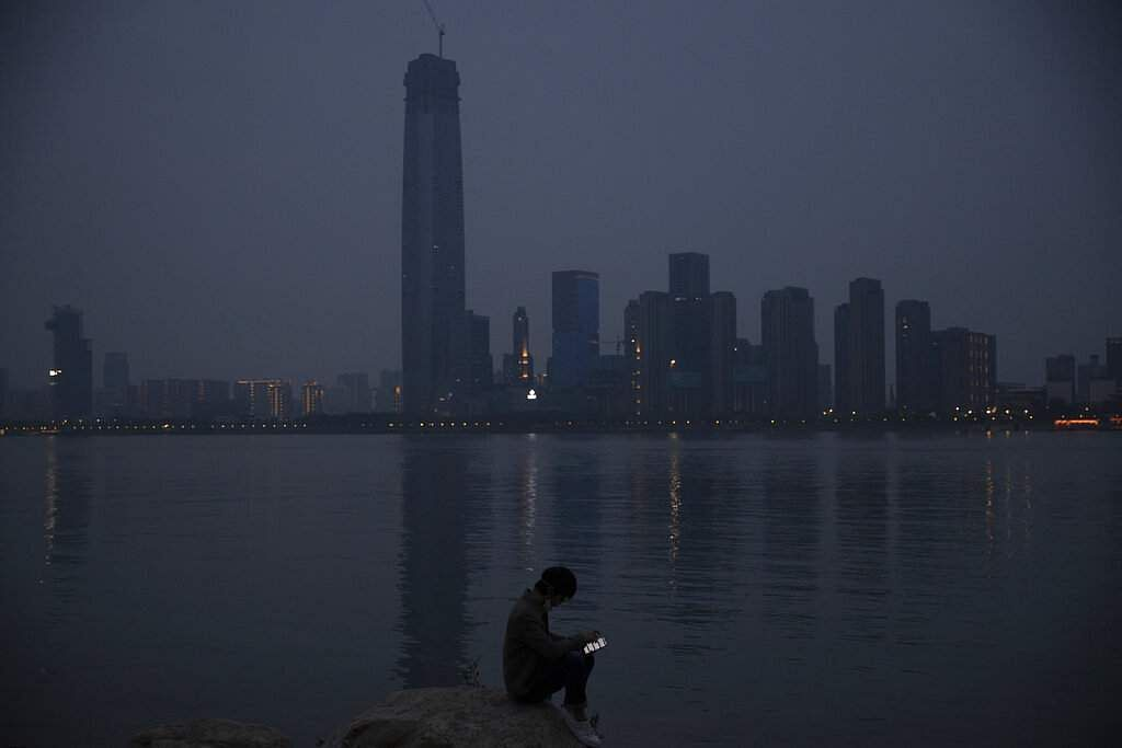 A man checks his mobile phone along the Yangtze River in Wuhan just as the Chinese city was at last released from virus quarantine. (AP Photo/Ng Han Guan)