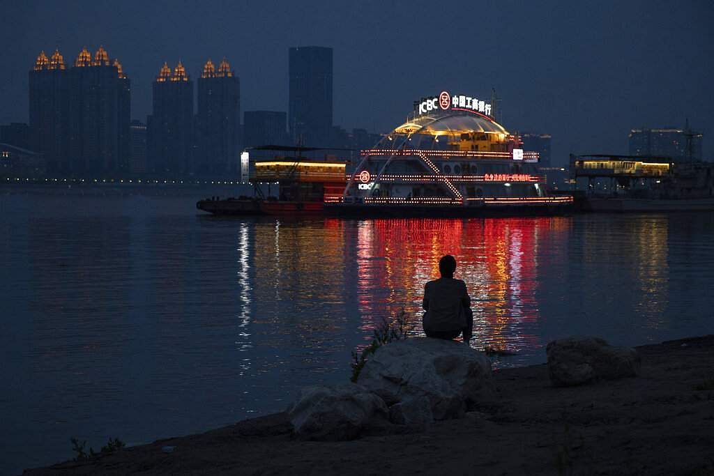 A man is silhouetted by lights reflected from a ferry along the Yangtze River in Wuhan just as the Chinese city was at last released from virus quarantine. (AP Photo/Ng Han Guan)