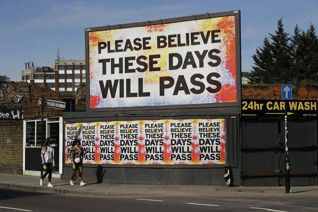 Women wearing face masks to protect themselves from the novel coronavirus walk past a billboard with a work by artist Mark Titchner in East London. (AP Photo/Matt Dunham)