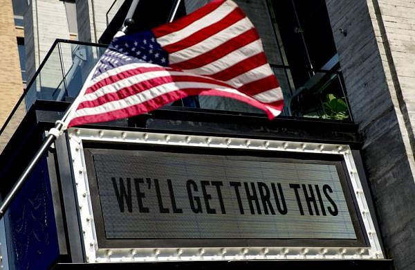 A sign at The Anthem music venue reads 'We'll Get Thru This' at the wharf, which is almost completely empty because of the coronavirus outbreak in Washington. (AP Photo/Andrew Harnik)
