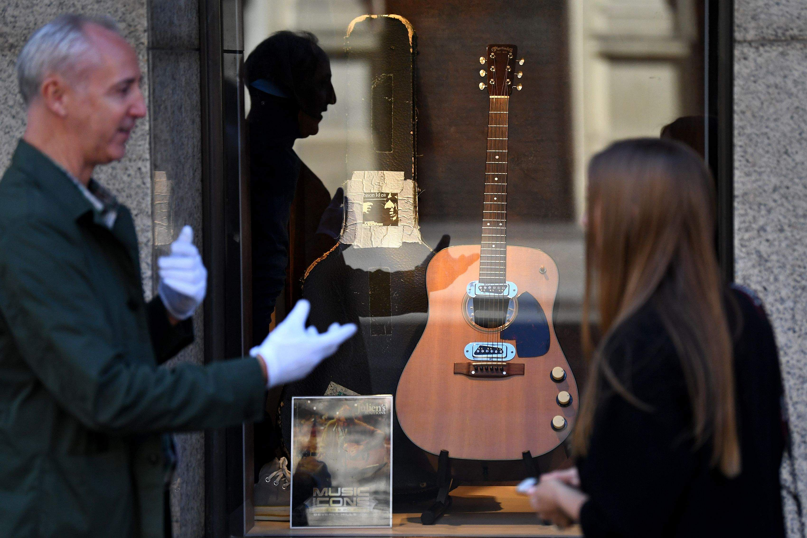 Co-owner of Julien's Auctions, Martin Nolan chats with a passer-by about the guitar used by Kurt Cobain in Nirvana's famous MTV Unplugged in New York concert in 1993. (Pic: AFP/DANIEL LEAL-OLIVAS)