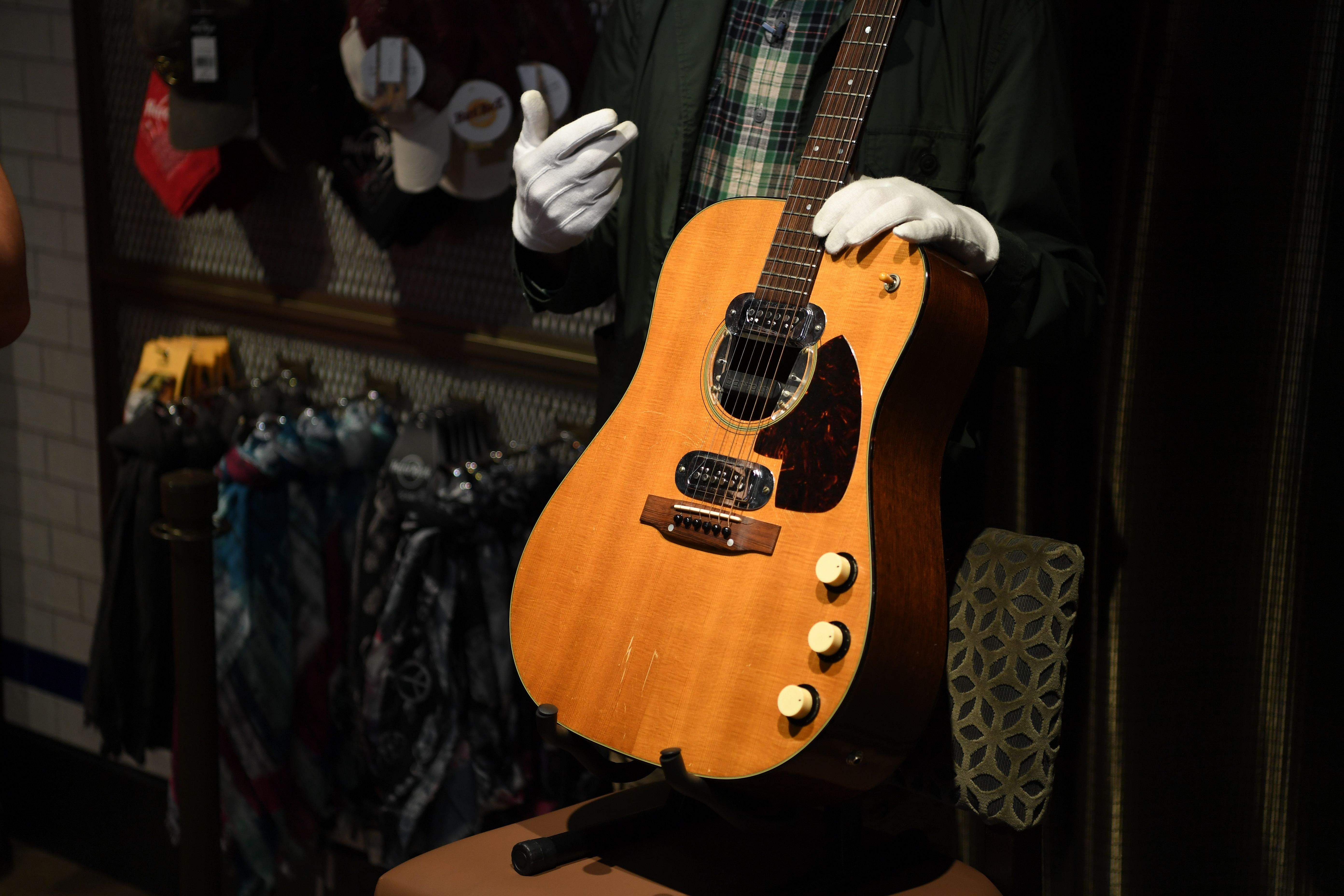 Co-owner of Julien's Auctions Martin Nolan displays Kurt Cobain's guitar at the Hard Rock Cafe Piccadilly Circus in central London. (Pic: AFP/DANIEL LEAL-OLIVAS)