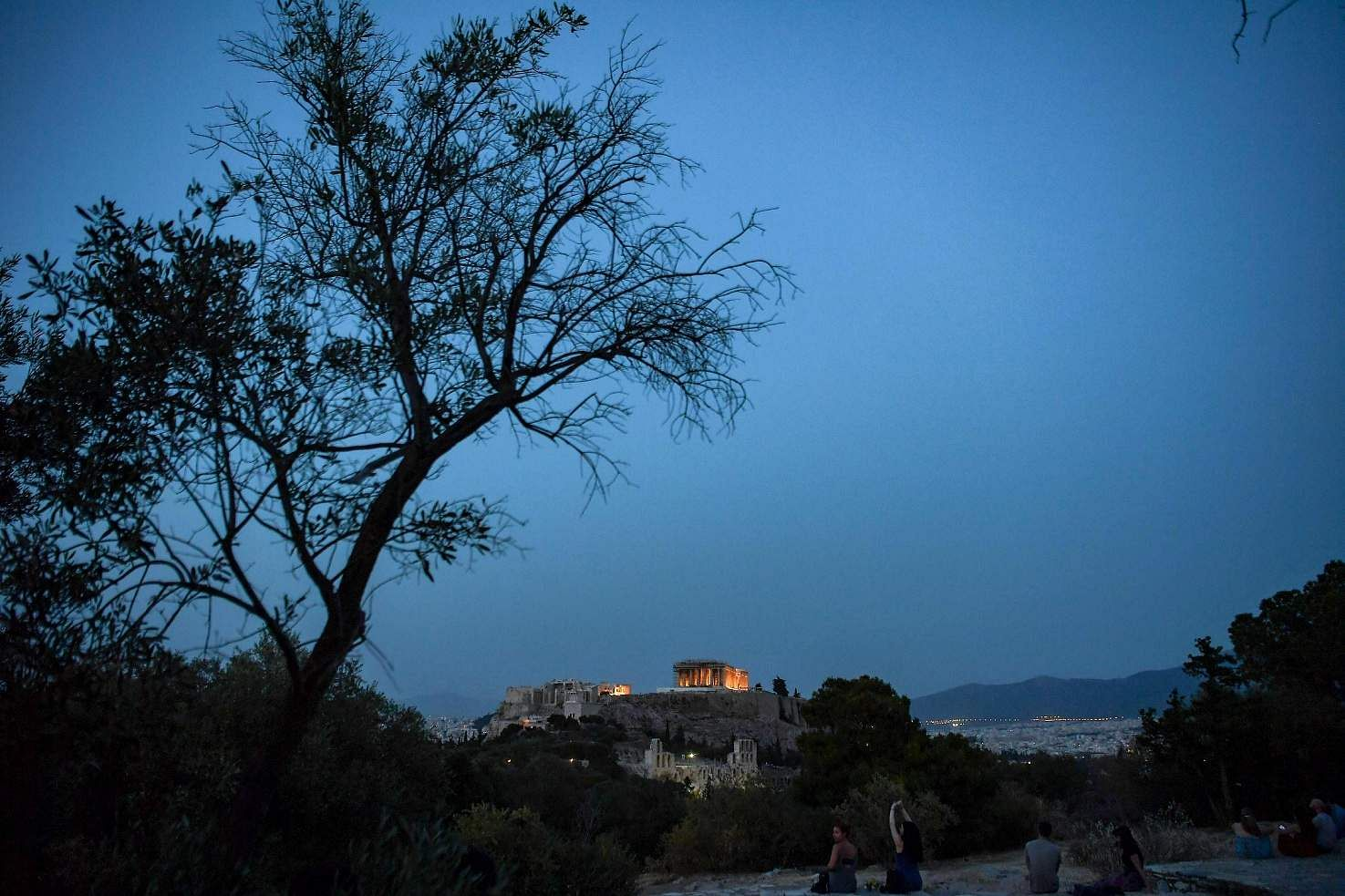 People sit on a hill facing the ancient Temple of Parthenon atop the Acropolis hill in Athens (AFP/ARIS MESSINIS)