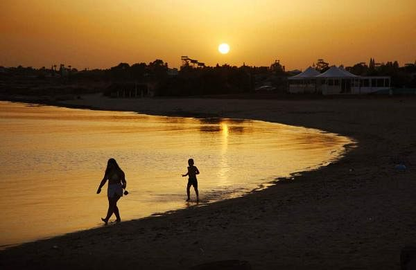 Beachgoers at sunset at an empty stretch of Dome beach hotel at Makrinissos in Cyprus' seaside resort of Ayia Napa. (AP Photo/Petros Karadjias)