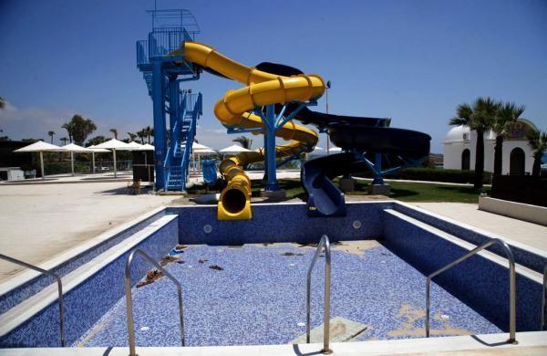 A swimming pool lays empty at a closed hotel at the popular Cyprus seaside resort of Ayia Napa. (AP Photo/Petros Karadjias)